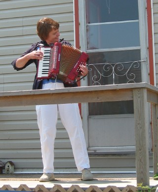 Eva Barnes directing the Estonian songs concert portion of the picnic with an old accordion she found rusting in her parents' basement  and which she taught herself to play. The sing-along of several well known old favourites was quite spirited.   Photo: Peeter Bush - pics/2006/13738_6.jpg