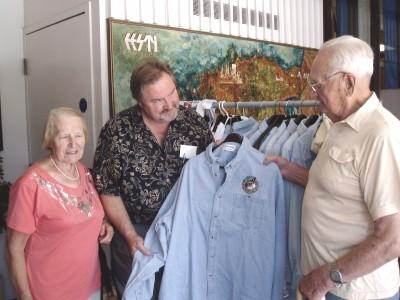 * Avo Kittask tutvustab poe külastajatele Virve Leesmaale ja August   Pertmannile Eesti temaatikaga rõivaid. Foto: K. Tensuda - pics/2006/13936_2.jpg