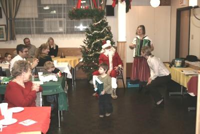 Jõuluvana jagas lastele kingitusi Ottawa Eesti Seltsi jõulupuul; dr Ülle Baum saatis akordionil jõululaule. Foto: Peeter Bush - pics/2006/14942_19.jpg
