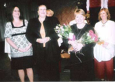 Kohalike kooride esindajad tänavad külakosti toojaid. Dirigent Heli Jürgenson lilledega. Foto: E. Purje  - pics/2007/10/17780_1.jpg