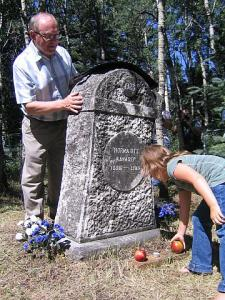 Seventh generation Estonian descendant places an apple at the gravestone of her Estonian ancestor, Horma Ott Kängsep, as AEHS president Bob Kingsep looks on, at Gilby, Alberta.  The stone was erected some years after Ott's death in Alberta in 1905.   Photo: Helgi Leesment. - pics/2008/10/21242_1_t.jpg