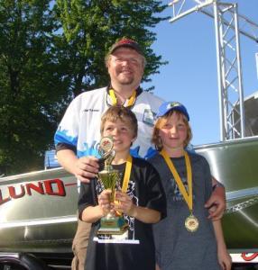 Jacob (vas.) ja Evan Küng koos oma isa Andrus Küngiga pärast autasustamist auhinnaks saadud paadi taustal.  Foto: erakogust - pics/2009/06/24048_1_t.jpg