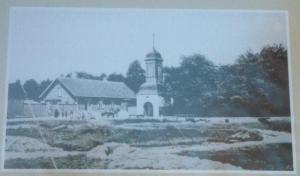 Vana foto Kalamaja kalmistu infotahvlilt: kellatorn ja kalmistuvahi maja omal ajal. Nüüd on maja asemel laste mänguväljak. - pics/2009/11/25866_3_t.jpg