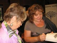 """Imbilt Imbile. Imbi Paju signeerib oma raamatut """"Memories Denied"""" Ellen  Leivati lapselapse jaoks. Foto: E. Purje - pics/2010/08/29417_2_t.jpg"""