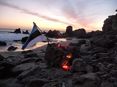 Photo description: A small group of Toronto Estonians visiting southern California on March 25, 2011 held a candle lighting ceremony at Corona del Mar,CA in memory of Estonian victims of Soviet deportations March 25, 1949.Photo shows candles and Estonian flag on shore of Pacific Ocean.  - pics/2011/03/31897_2_t.jpg