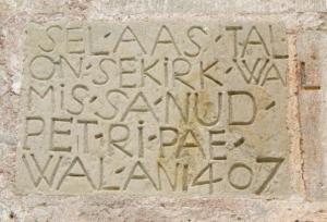 """Saaremaa keskel asuv Kaarma Püha Peetri ja Pauli kirik on Lääne-Eesti suurim ja kujundusrikkaim sakraalhoone. Kiriku peaukse kõrvale on müüritud kivitahvel tahutud sõnadega: """"SEL-AAS-TAL-ON-SEKIRK-WAL-MIS-SA-NUD-PET-RI-PAE-WAL-AN1407"""". Väidetakse, et need on vanimad teadaolevad eestikeelsed kirjaread. Esimene katkendlikult säilinud eestikeelne raamat on Tallinna pastorite Wanradti ja Koelli 1535. a. trükitud luterlik katekismus. Foto: Riina Kindlam - pics/2011/10/33623_1_t.jpg"""
