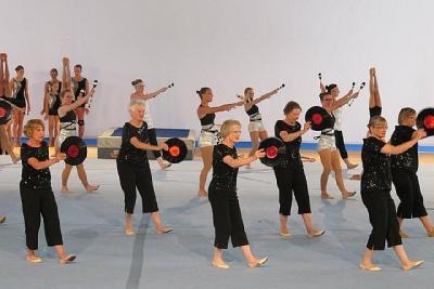"""# 1 Calgary NorGlen naisvõimlejad koos mitme klubi võimlejatega esitamas kava  """"Press Play"""". Võimlemisvahenditena kasutatakse heliplaate kui üht faasi muusika esitamise tehnoloogia arengust. Foto: Lindsay Oliver  - pics/2011/10/33747_1_t.jpg"""
