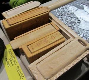 Väiksed piklikud puidust kastikesed, nikerdustega kaunistatud ja erilise LÜKANDkaanega. Justkui väike puusärk... Kas majahaldja Tõnni vakk? Kuressaare Ametikooli õpetaja seletas, et see on KÜÜP ning ühest puunotist voolitud. Küübis hoiti vanasti tarbeasjakesi, eeskätt aga reisile minnes küünlaid, mil see toimis ka küünlahoidjana. Põlev küünal pisteti lükandkaane vahele püsti seisma. Fotod: Riina Kindlam  - pics/2011/11/34096_3_t.jpg