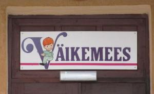 """Seen on a street in the north-eastern Estonian city of Kohtla-Järve. What could be behind a door with a sign above it reading Väikemees (Little Man)? The building is surrounded by an enclosed yard and has playground equipment in the back. My first thought: """"Could this be a private boys kindergarten?"""" Photo: Riina Kindlam   - pics/2012/05/36260_003_t.jpg"""