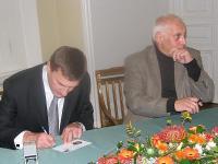 Peaminister Andrus Ansip ja graafik Lembit Lõhmus esimese päeva ümbrikule autogramme jagamas. - pics/2012/09/_002_t.jpg