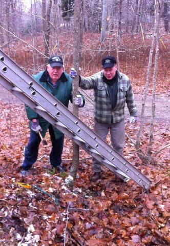 Mihkel Lõugas, kirves käes, on üks neist meestest kes Kotkajärvel on 60 aastat käinud talgutöid tegemas. Puid tuleb ju maha võtta, et redelit saaks õige nurga alla asetada! Tõnu Naelapea võib vaid loota, et tal Mihkli taolist sisu ja vastupidavust oleks. Eeskuju õpetab, põlvest põlve. Foto: TK  - pics/2012/11/37877_001_t.jpg