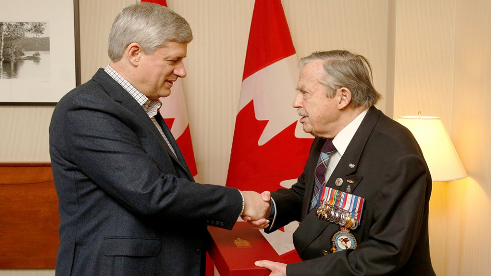 Charlesbourg, QC – Prime Minister Stephen Harper, joined by Steven Blaney, Minister of Public Safety and Emergency Preparedness, presents a Canadian Flag to Jean Cauchy, a veteran of the Second World War, in honour of National Flag of Canada Day. (PMO photo by Jason Ransom) Date: February 15, 2015 - pics/2015/02/44397_001.jpg