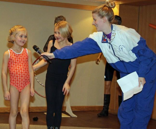 "Amicitia's ""esinaine"" and former gymnast Kristina Põldre pursuading mini-gymnasts Imbi and Eila Uukkivi to demonstrate a few of their favourite gymnastics moves at Küünlapäev. - pics/2015/03/44526_002.jpg"