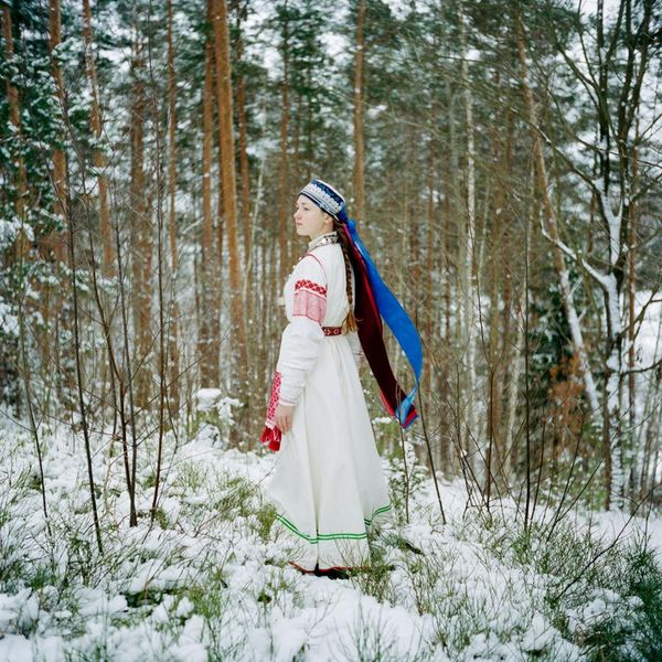 """In Obinitsa, Estonia, a young Seto girl named Liisi Lõiv wears a traditional costume in her grandparents' garden. Seto women typically have both an old costume and a new one. This is an older one—white, with long, rolled sleeves. The clothing reveals other details too. A married woman must cover her hair, while an unmarried young woman or girl like Liisi will wear only a garland or a headscarf, leaving her long braid visible. Today Setos wear their traditional clothes only on special occasions. Liisi says she embroidered this costume herself. """"I'm proud of being Seto,"""" she says. """"It is where I come from, where I grew up."""" Photograph by Jérémie Jung - pics/2016/11/48673_001.jpg"""
